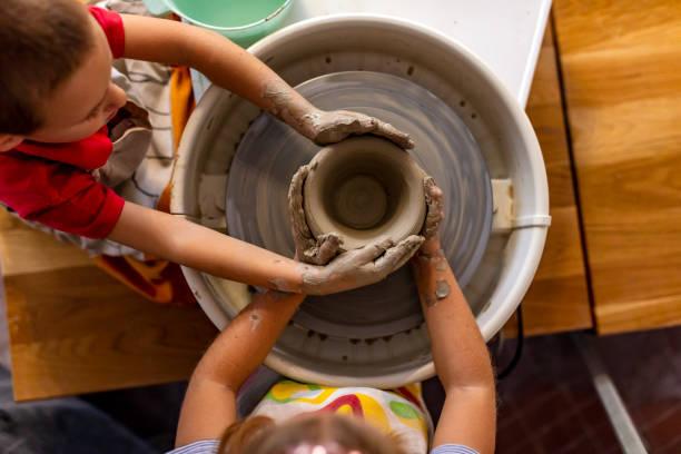 four hands working on pottery wheel - teacher school solo imagens e fotografias de stock