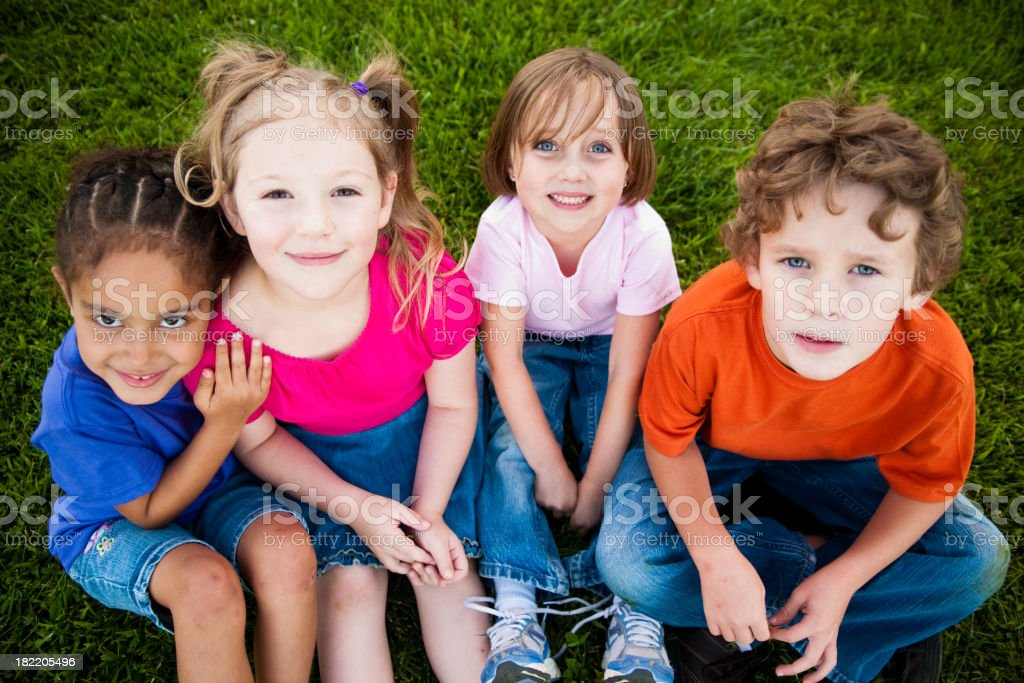 Four Happy Children Sitting in the Grass royalty-free stock photo