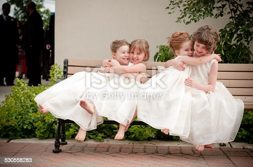 Color photo of four happy little flower girls sitting together and hugging while wearing formal dresses. They are sisters and cousins.