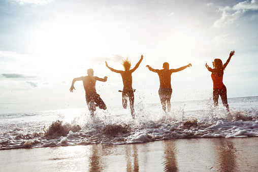 Four happy friends having fun and runs to sunset sea beach. Space for text