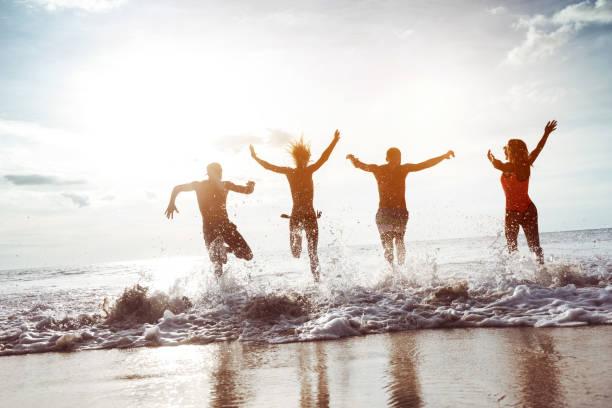 幸せな 4 人の友人は、サンセットビーチ ストックフォト