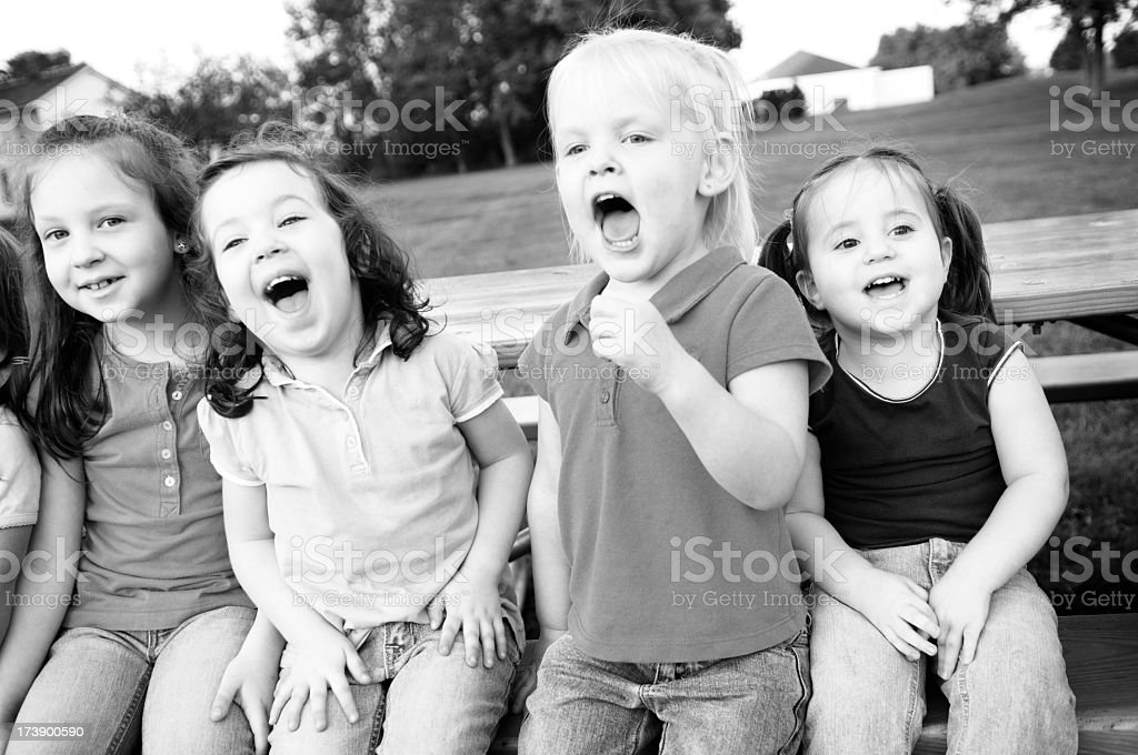 Four Happy Girls Laughing and Sitting at a Picnic Table royalty-free stock photo