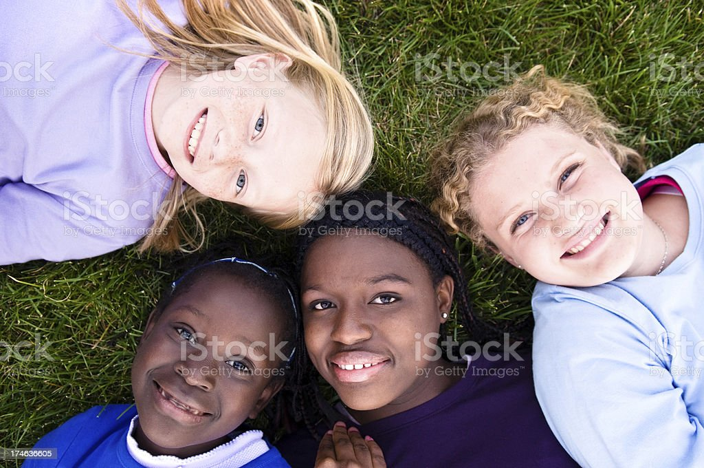 Four Happy Girls Lying in the Grass royalty-free stock photo