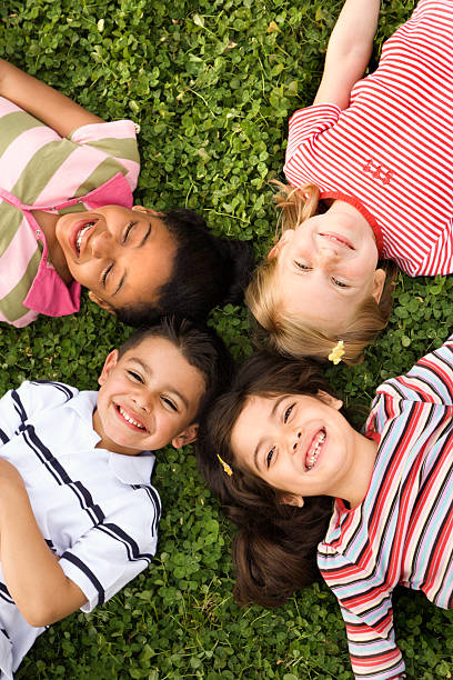 Four happy kids laying with heads together outside in clover stock photo