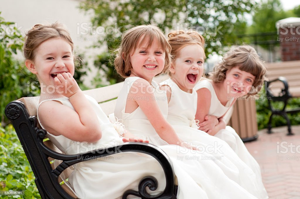 Four Happy Little Flower Girls Laughing Together in Formal Dresses stock photo