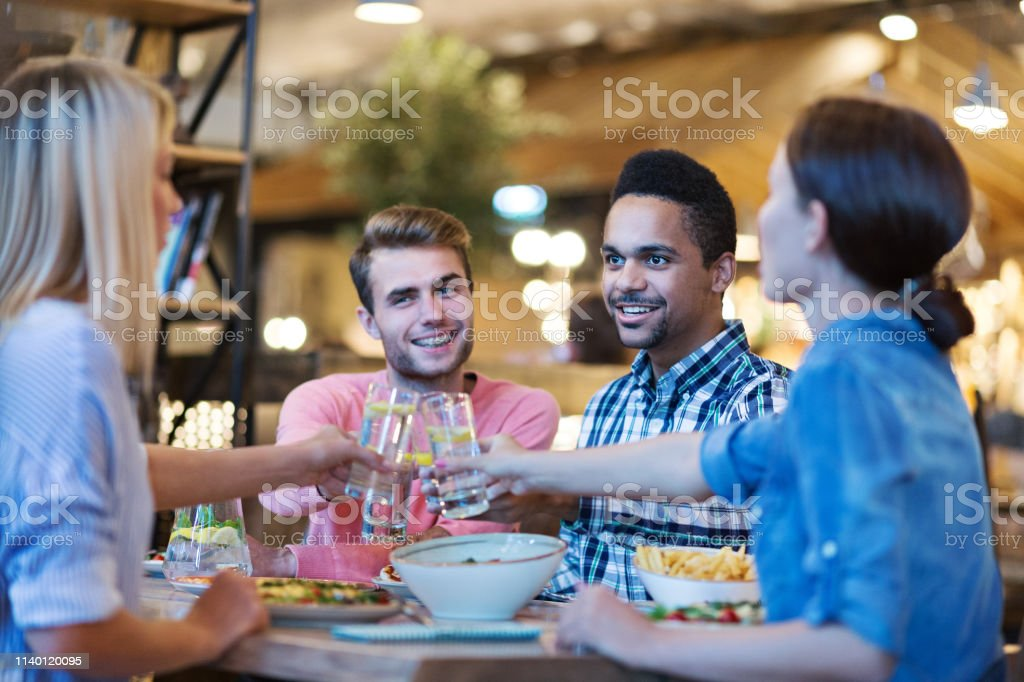 Four happy multi-ethnic friends gathering together for dinner and...