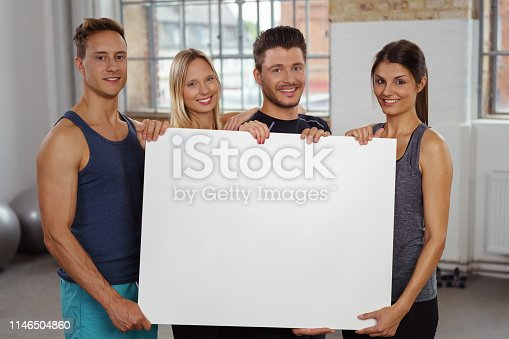 istock Four happy people holding large blank white poster 1146504860