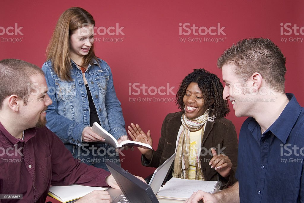 Four happy students working on school work together royalty-free stock photo