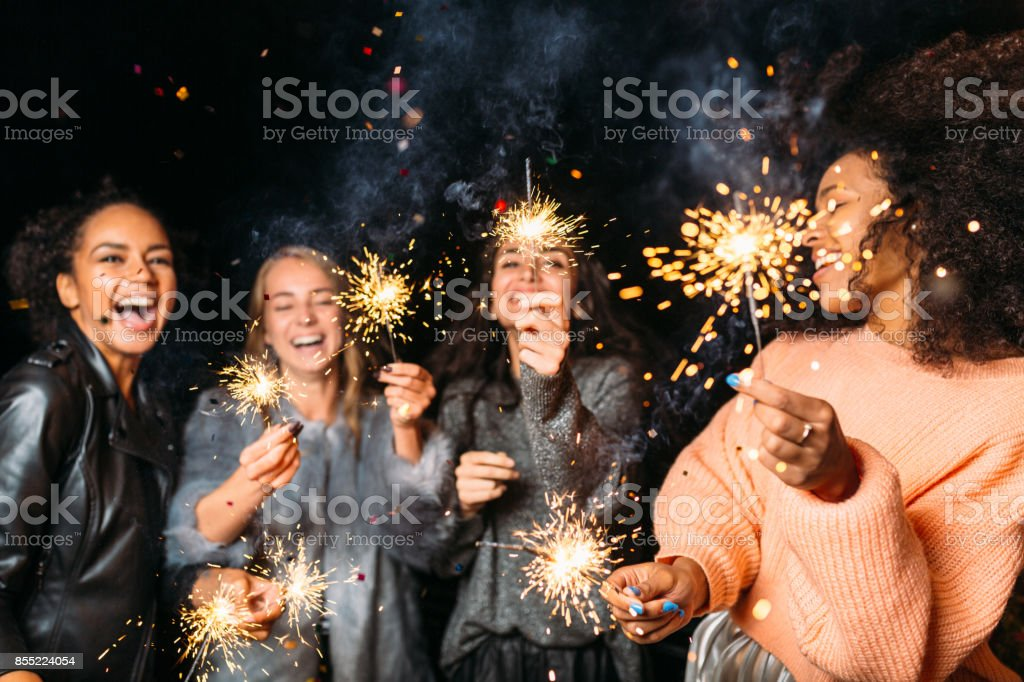 Four happy women holding sparklers, throwing confetti royalty-free stock photo