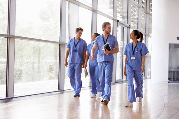 Four healthcare workers in scrubs walking in corridor stock photo