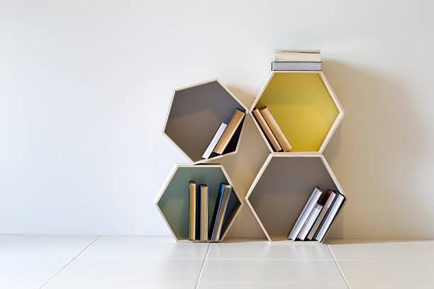 vier sechseck geformte dekorativen regalen speichern und anzeigen von büchern - kreativer speicher stock-fotos und bilder