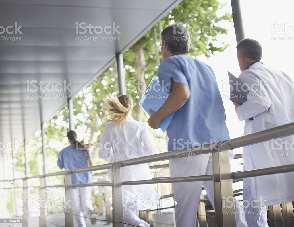 Four hospital workers running down corridor royalty-free stock photo