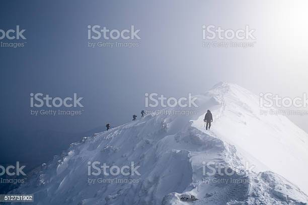 Photo of Four ice climbers scaling a mountains summit