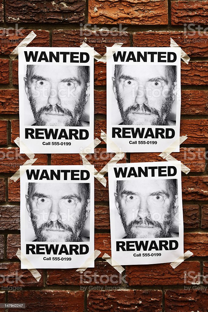 """Four identical """"Wanted"""" posters of wild eyed man on wall royalty-free stock photo"""