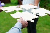 istock Four individuals unite with giant puzzle pieces 175514259