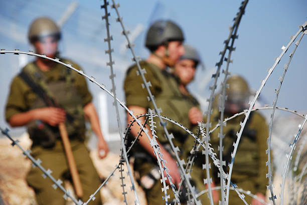 Razor Wire and Soldiers Four Israeli soldiers stand behind razor wire near the Palestinian village of Bil'in in the West Bank historical palestine stock pictures, royalty-free photos & images