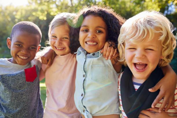 quattro bambini in giro insieme in giardino - bambino foto e immagini stock