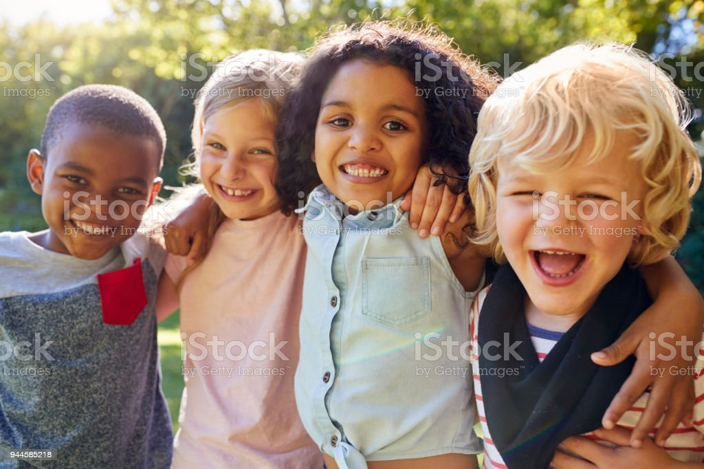 Four kids hanging out together in the garden stock photo