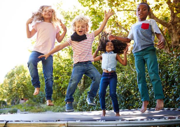 cuatro niños que se divierten juntos sobre una cama elástica en el jardín - trampolín artículos deportivos fotografías e imágenes de stock