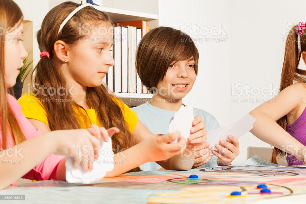Four kids playing cards for a pastime stock photo