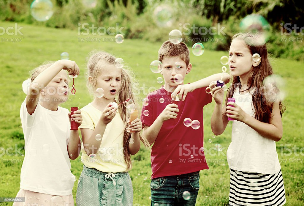 Four  kids sitting together and blowing soap bubbles royalty-free stock photo