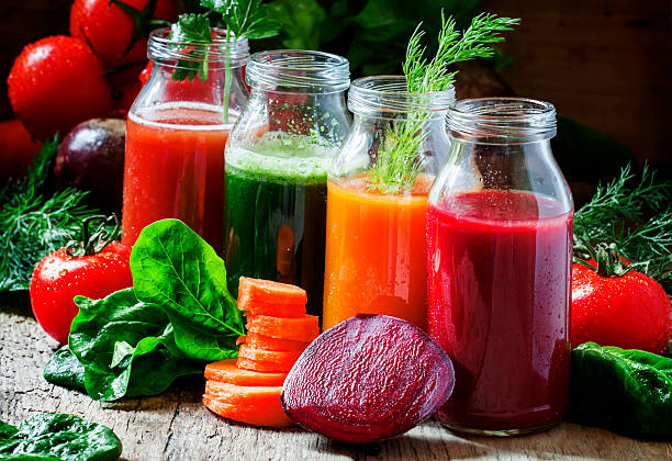 Four kind of vegetable juices: red, burgundy, orange, green stock photo
