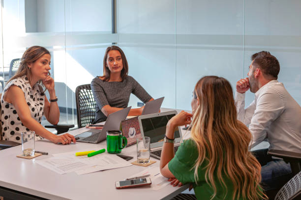 Vier Angestellte der lateinamerikanischen Millennial-Generation bei einem Geschäftstreffen in einem Büro mit Laptops und anderer Technologie; Sie sind alle in lässiger Kleidung gekleidet. Kopierraum – Foto