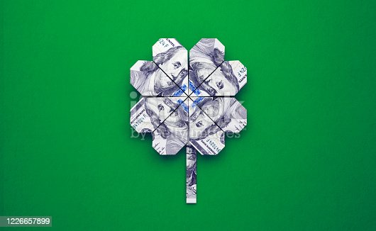Four leaf clover made of one hundred Turkish Lira banknotes over green background. Horizontal composition with copy space. Finance and luck concept.