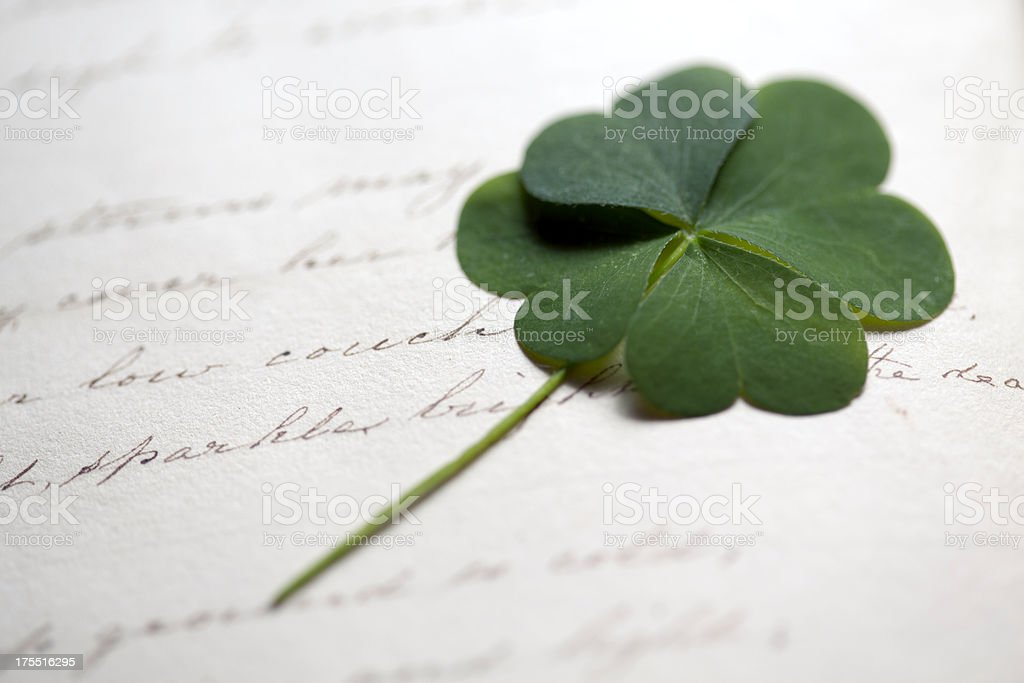 Four Leaf Clover on Antique writing stock photo