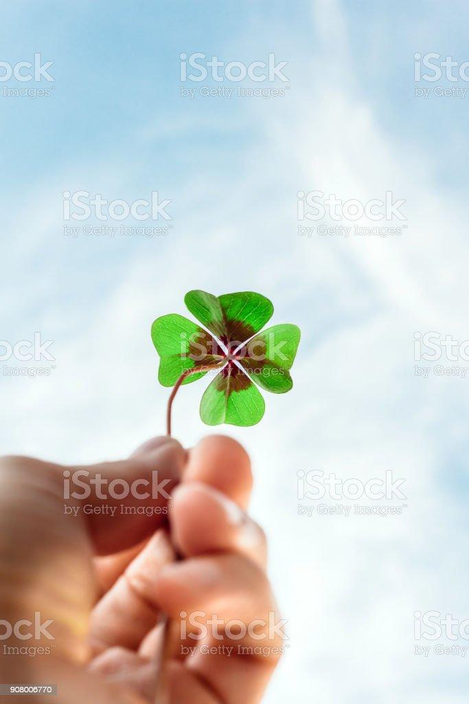 Quatro trevo sorte realizada com a mão contra o céu - foto de acervo