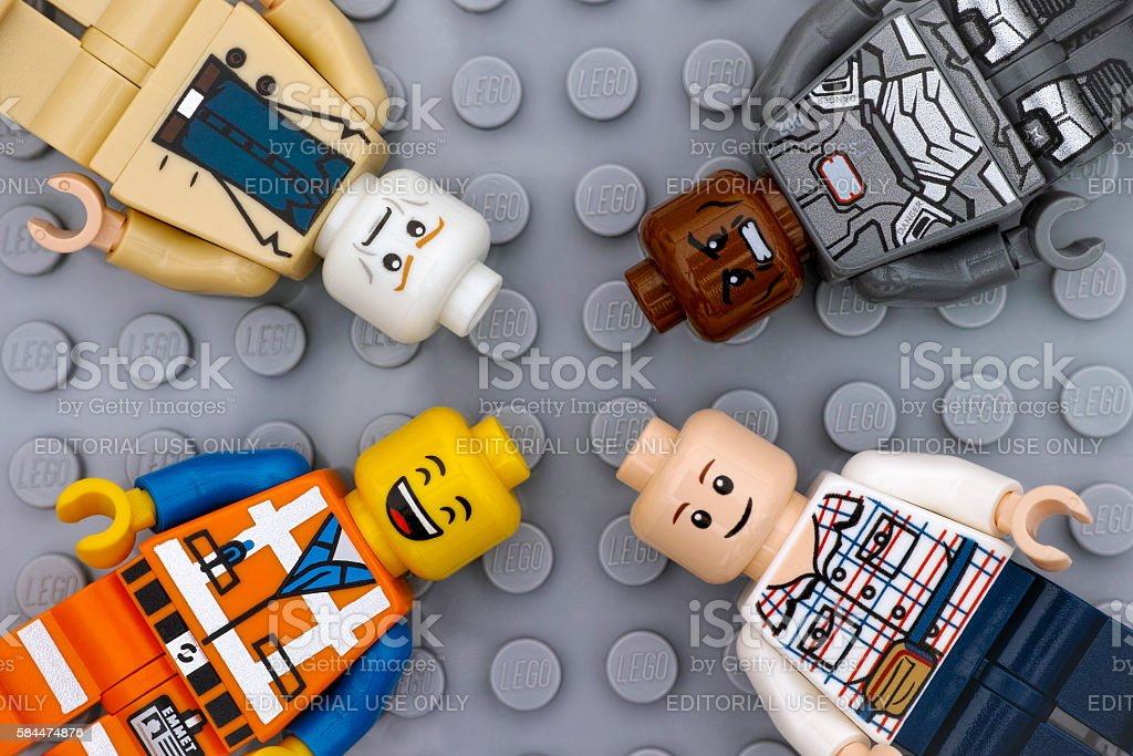 Four Lego minifigures with with different color heads and emotions stock photo