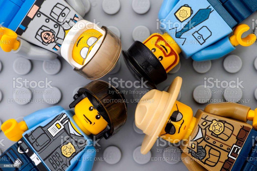 Four Lego policemen minifigures on gray baseplate royalty-free stock photo