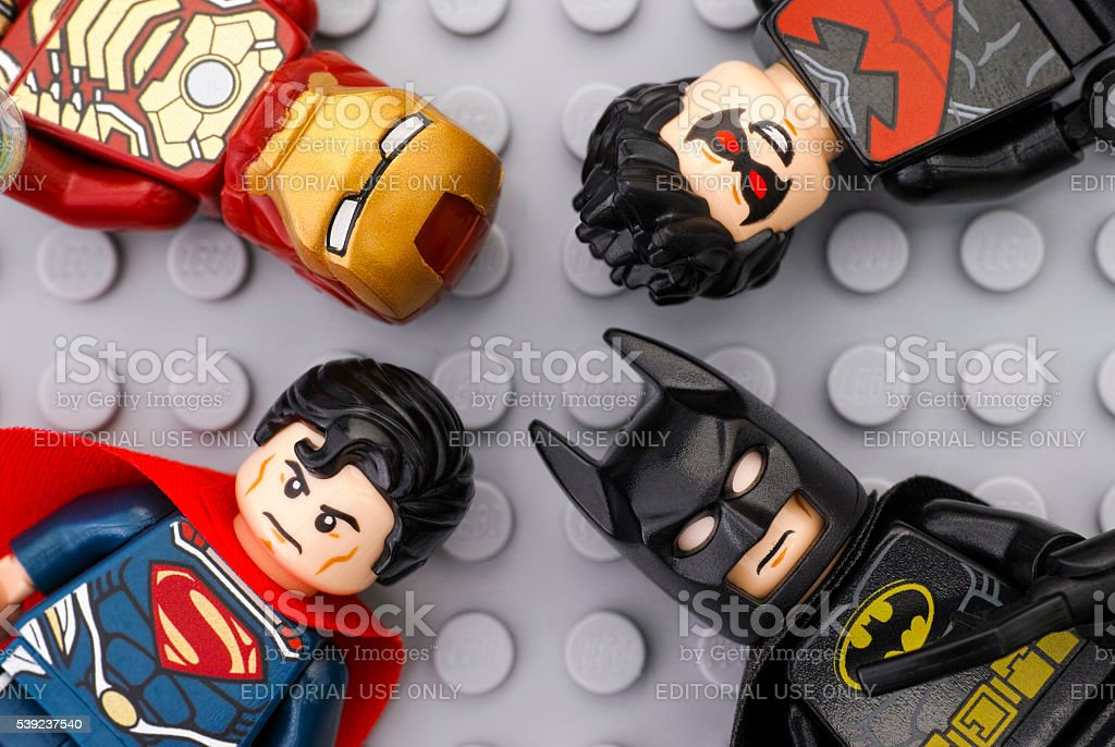 Four Lego Super Heroes minifigures on gray baseplate stock photo