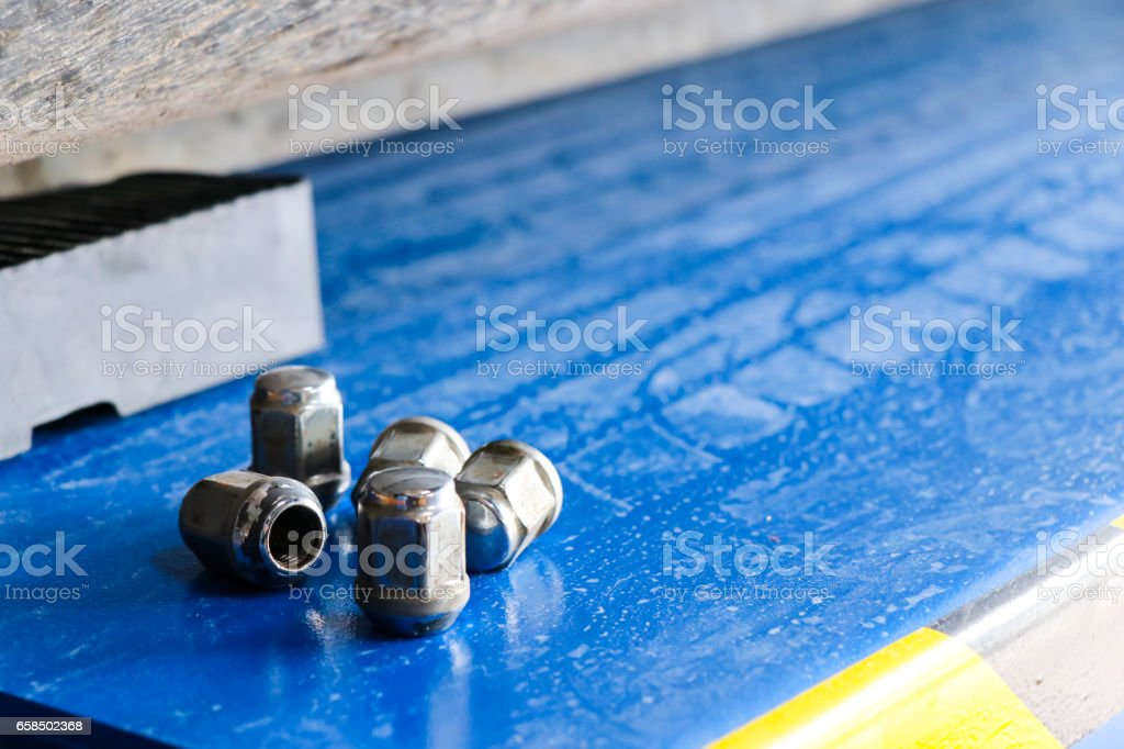 four lug nuts on the ground when replacing wheels/Wheel equipment stock photo