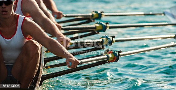 istock Four male athletes rowing across lake in late afternoon 861213906