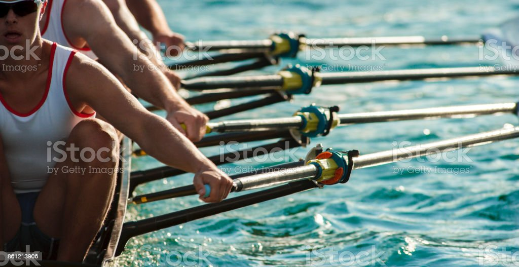 Four male athletes rowing across lake in late afternoon stock photo