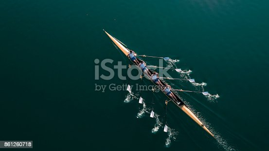 istock Four male athletes sculling on lake in sunshine 861260718
