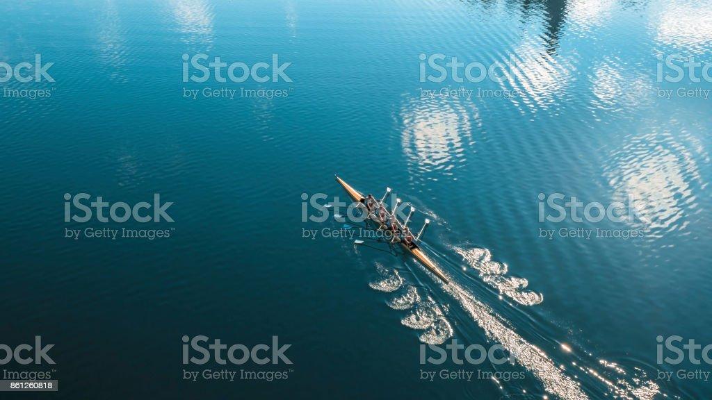 Four male athletes sculling on lake in sunshine stock photo
