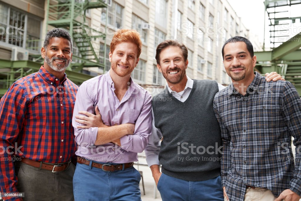 Four male coworkers smiling to camera outside stock photo