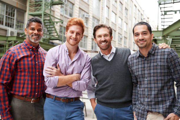 four male coworkers smiling to camera outside - men stock pictures, royalty-free photos & images