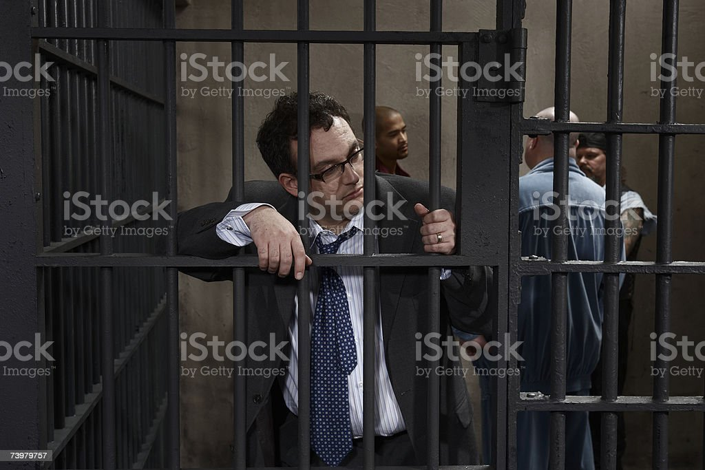 Four men in prison cell, one leaning against bars stock photo