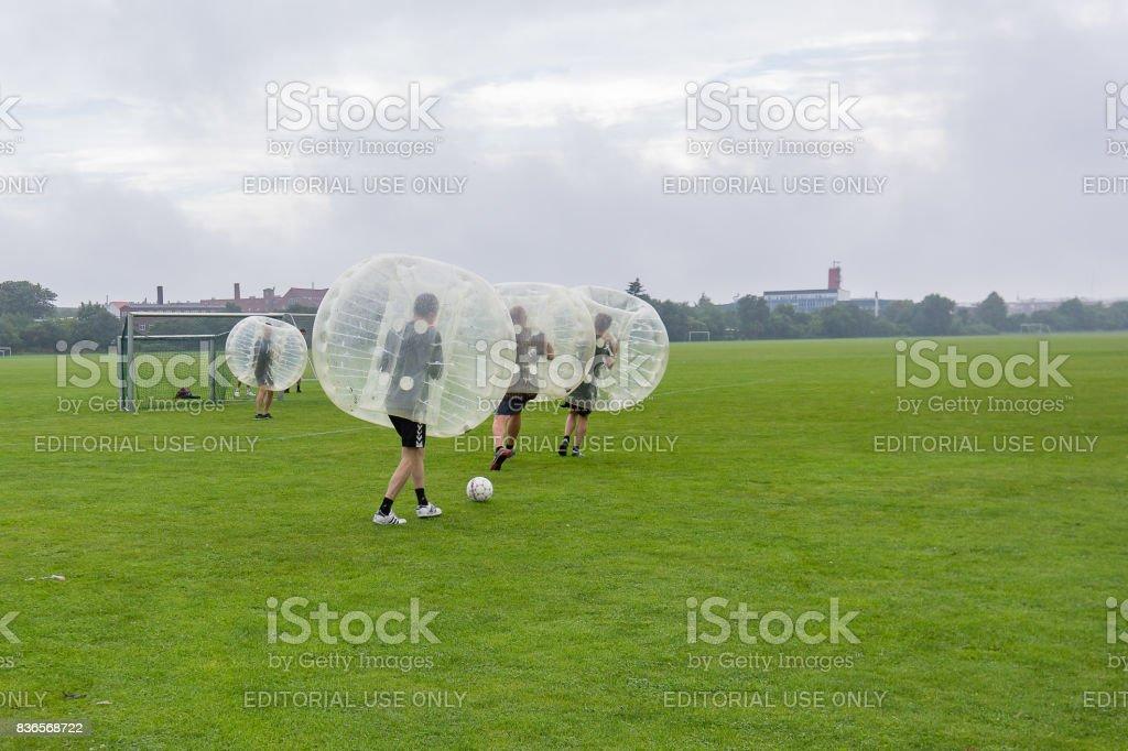 Quatro homens jogando futebol em um bumperball - foto de acervo