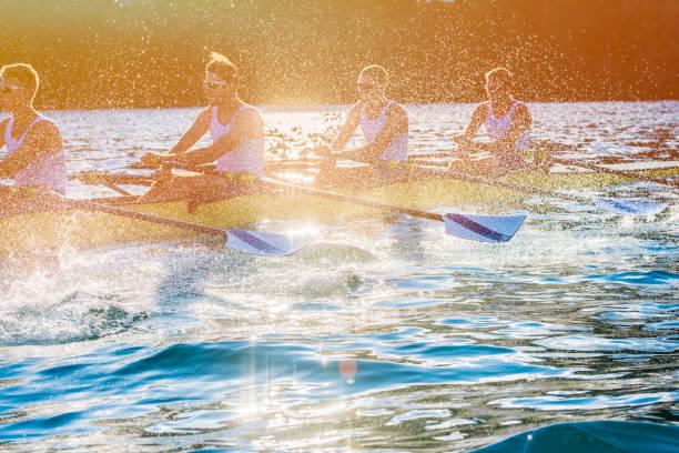 4 人の男性が湖に漕ぎ - パドルスポーツ ストックフォトと画像