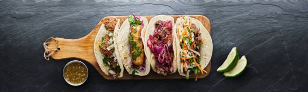 four mexican street tacos with fish barbacoa and carnitas shot in panoramic composition stock photo