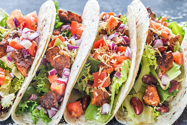 Four mexican tacos on a black background stock photo