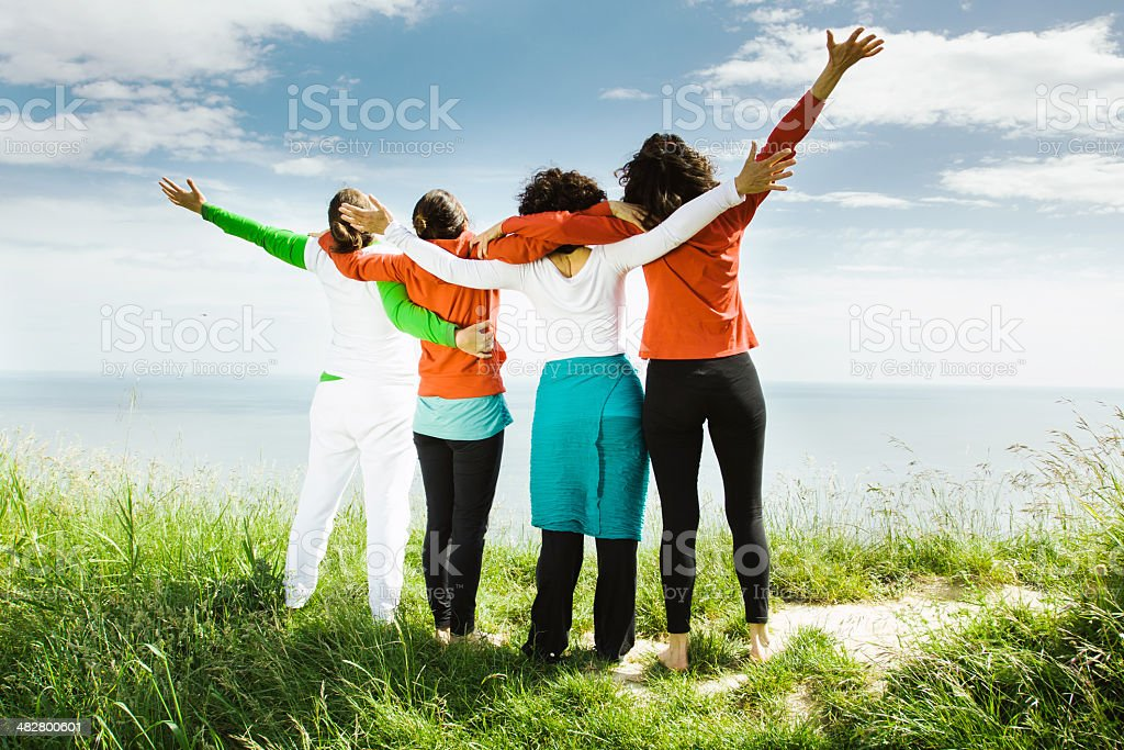 Four Middle age women open arms outdoors stock photo