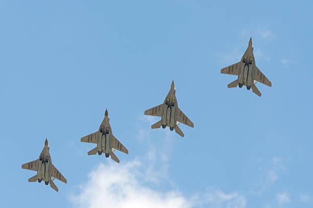 Cuatro MiG - 29 aeronaves militares volando sobre la plaza roja - foto de stock