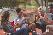 Four millennial friends play cards at their campsite