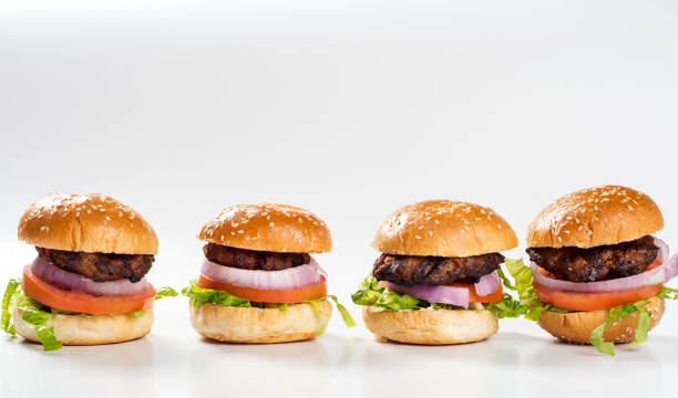 four mini burgers in a plate, barbecued meat, onion slice, tomato slice, lettuce leaves and roasted bread mini burger slider burger stock pictures, royalty-free photos & images