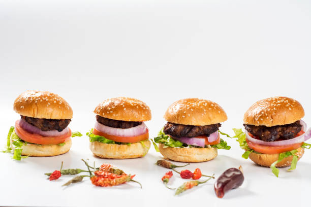 four mini burgers in a plate, barbecued meat, onion slice, tomato slice, lettuce leaves and roasted bread with dry pepper mini burgers with peper on the white background slider burger stock pictures, royalty-free photos & images